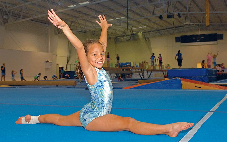 Girl doing the splits on a mat during gymnastics practice.