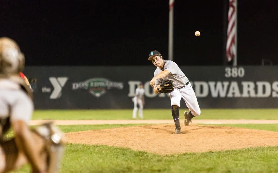 baseball player throwing the ball at a night game